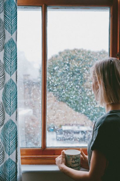 woman-gazing-out-window-into-snow